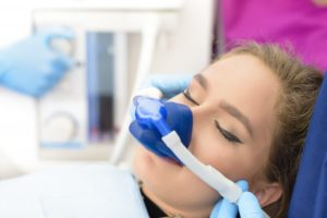 a young woman wearing a nasal mask and receiving nitrous oxide during an appointment
